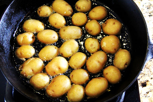 When the oil is hot, arrange the potatoes in a single layer, cut-side down.
