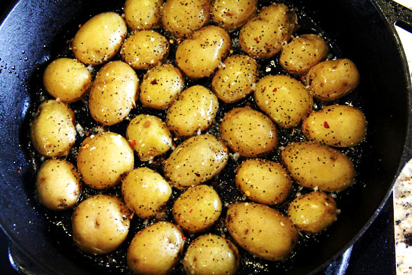Season the potatoes with a generous pinch of coarse sea salt, crushed red pepper flake, and black pepper. Notice how the oil is nearly soaked up? Awwww sookie sookie now!