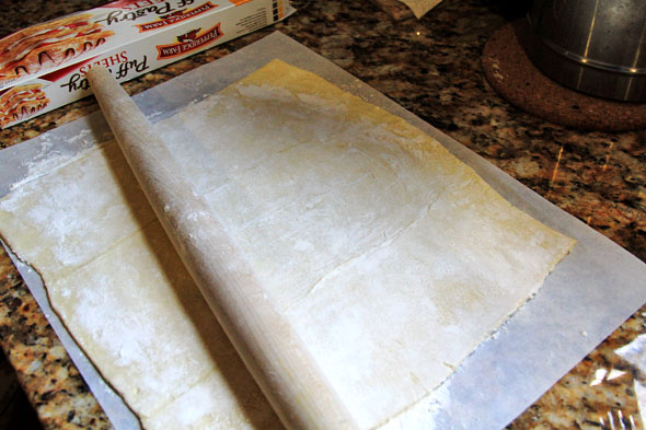 Thaw your puff pastry dough at room temperature until pliable (about a half hour, depending on the temperature in your kitchen). Flour your work surface, hands, and rolling pin and roll pastry out to a larger rectangle, making sure to connect the seams so it's all one piece.