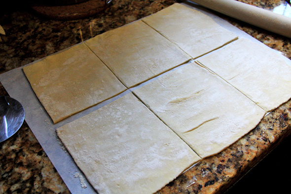With a very sharp knife or pizza cutter, cut the sheet of dough into 6 squares (if using a jumbo muffin tin, cut into 12 squares if using a regular size muffin tin). Roll each square so that it's large enough to fit into your muffin tins.