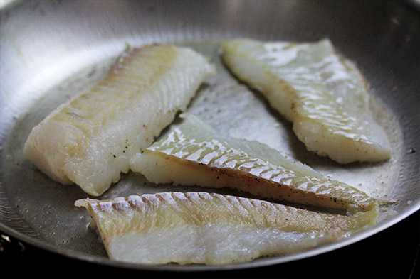 gently place each piece of fish down, making sure there's enough oil underneath every piece so it doesn't stick too badly.
