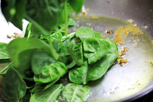 reduce the heat to medium, and don't scrape up what's left from the fish, leave it in there. maybe add another tablespoon or so of oil if needed, but start to pile the spinach into the pan.