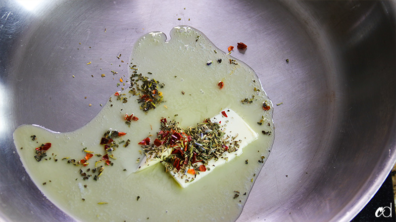 butter melting with crushed red pepper and herbs de provence