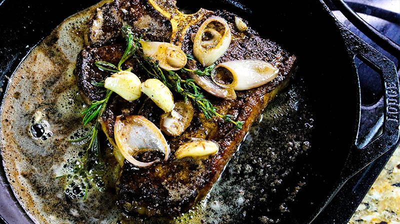 basting porterhouse steak with butter and herbs