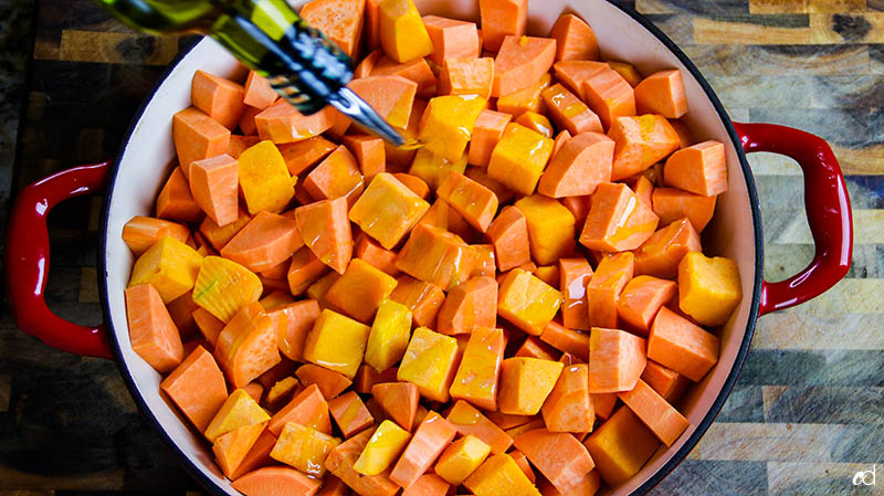adding olive oil to sweet potatoes and butternut squash
