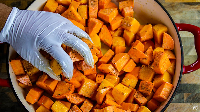 adding salt and pepper to sweet potatoes and butternut squash