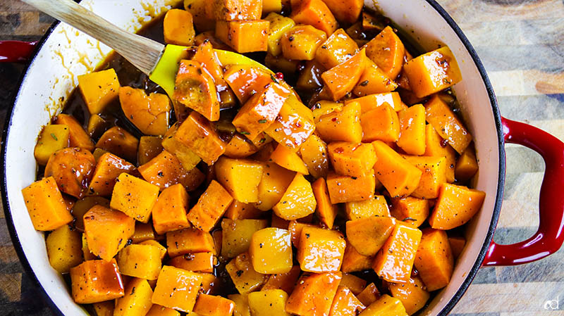 tossing roasted sweet potatoes and butternut squash with savory caramel